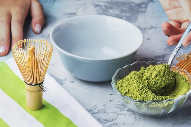 Garota coloca matcha em pó com uma colher de chá. o processo de fazer chá verde
