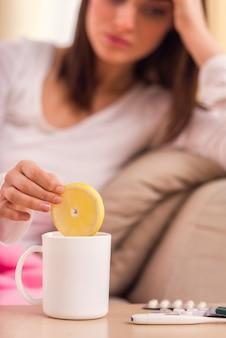 Garota coloca um limão em um copo e está doente.