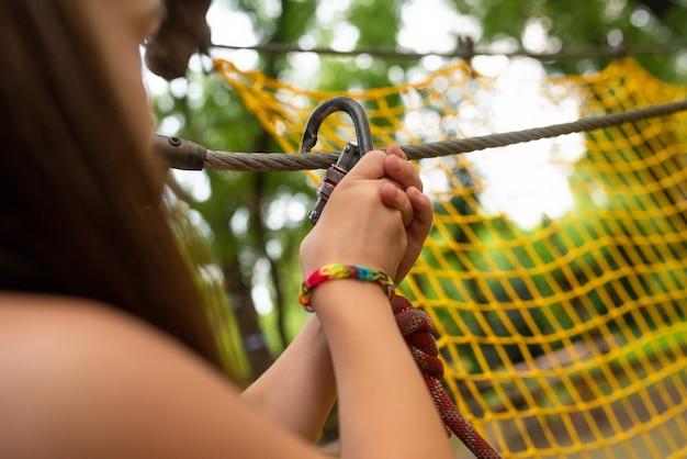 Garota coloca um mosquetão em uma corda em um parque de corda