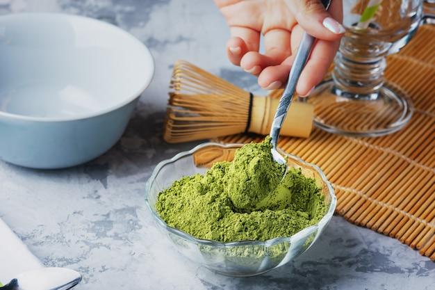 Garota coloca uma colher de chá de pó de chá verde em uma tigela. matcha chá verde em pó, bata e tigela.