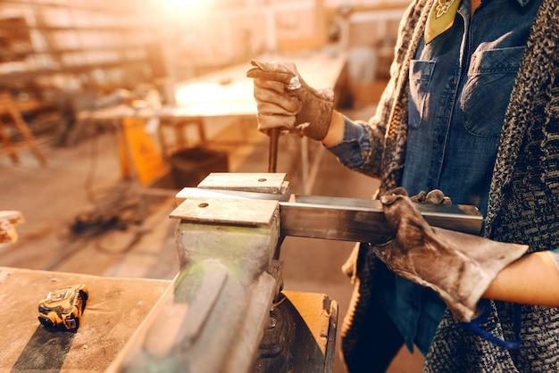 Garota colocando a haste de metal no espremedor usando luvas de proteção.