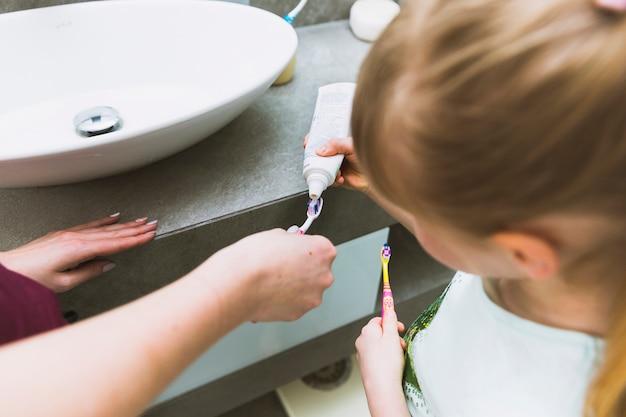 Garota colocando creme dental no pincel de mãe