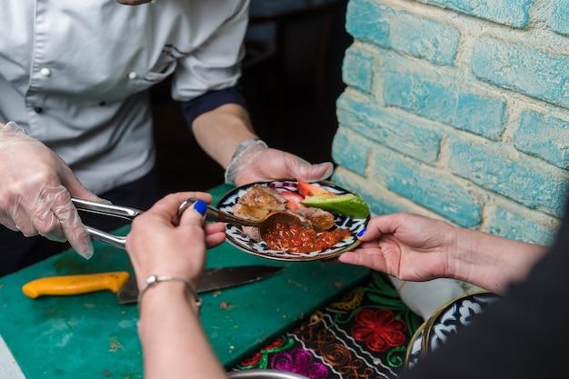 Garota colocando molho em um prato com carne e vegetais