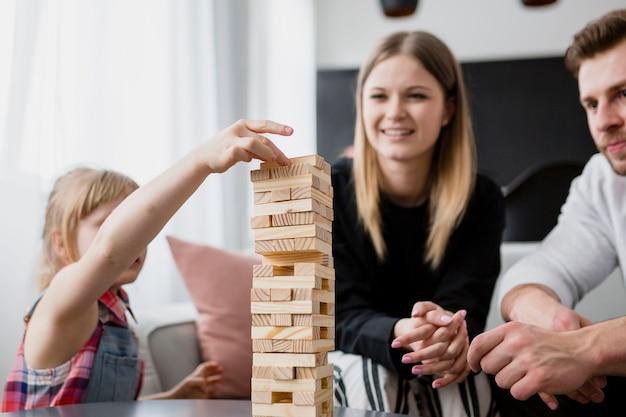 Garota colocando o bloco na torre perto de pais