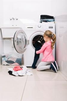 Garota colocando roupa suja na máquina de lavar roupa