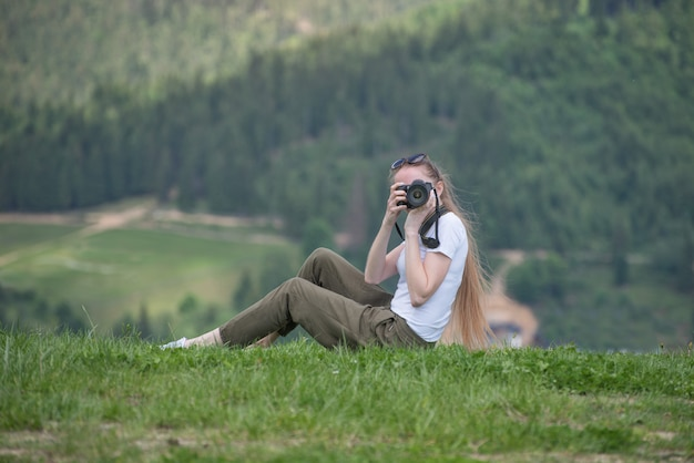 Garota com a câmera senta-se em uma colina e fotografias. floresta no fundo