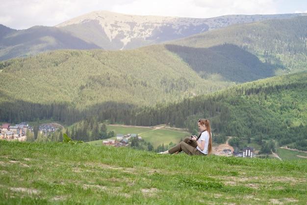 Garota com a câmera senta-se numa colina e visualizar fotos. montanhas ao fundo