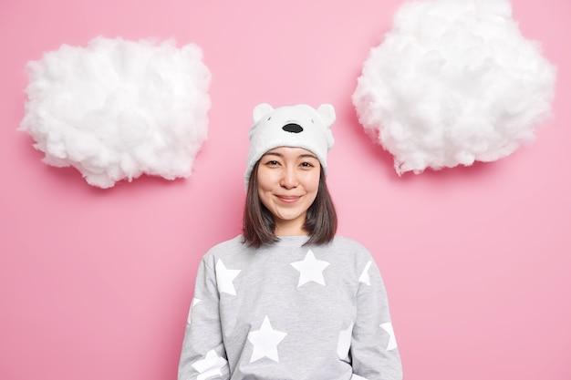 Garota com aparência oriental sorri suavemente usando um pijama confortável e chapéu se preparando para ir para a cama isolado em rosa