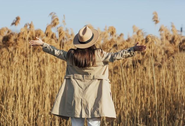 Garota com as mãos para cima no fundo de juncos fofos e céu azul