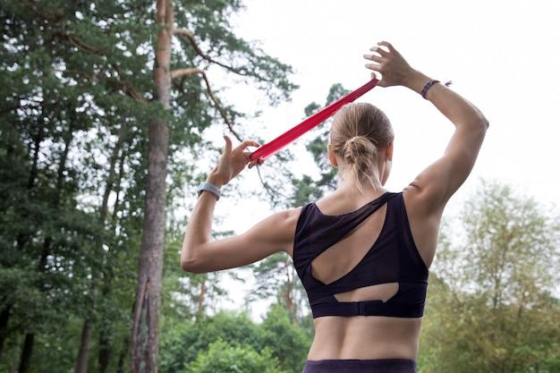 Garota com blusa e leggings treina com corda elástica vermelha em quadras esportivas no parque