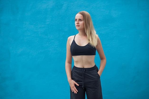 Garota com blusa preta esportiva na parede azul
