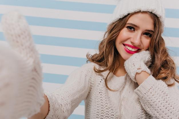 Garota com bom humor de inverno feliz faz selfies, tocando seu rosto com as mãos em luvas quentes. jovem modelo sorri modestamente, olhando