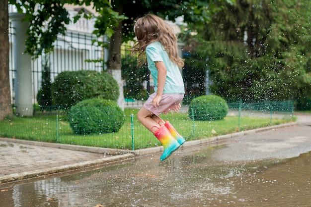 Garota com botas de borracha arco-íris pulando em poças perto de casa