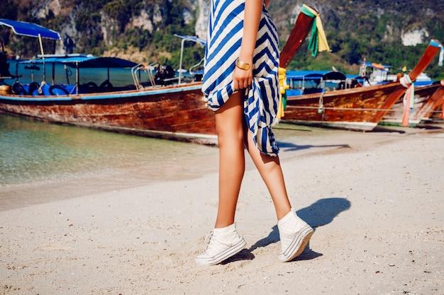 Garota com botas de couro brancas e vestido longo, pulando e se divertindo na bela praia da tailândia.