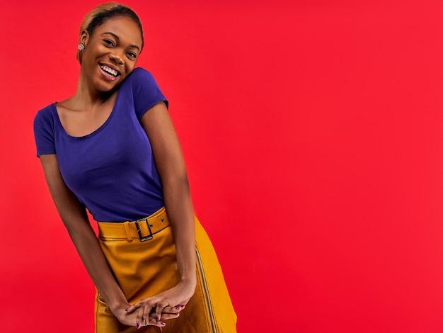 Garota com brincos em uma camiseta azul e uma saia amarela posando
