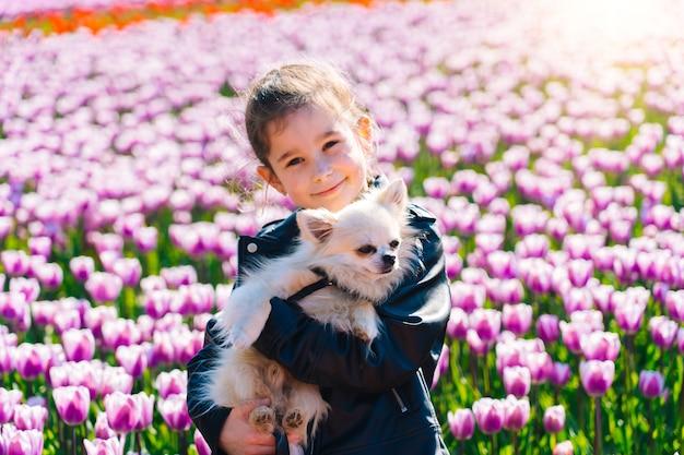 Garota com cabelo comprido cheirando a flor de tulipa em campos de tulipas