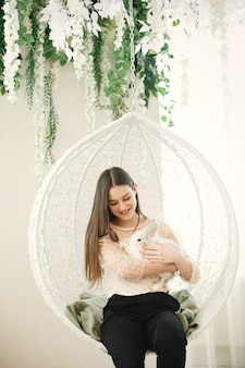 Garota com cabelo comprido. coelho branco nos braços da menina.