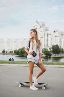 Garota com cabelo comprido com skate fotografando na câmera. rua, esportes ativos