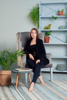 Garota com cabelo comprido em jeans e jaqueta posando na poltrona na sala de estar