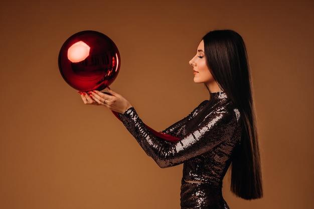 Garota com cabelo comprido em um vestido brilhante com uma grande bola de natal em um marrom.
