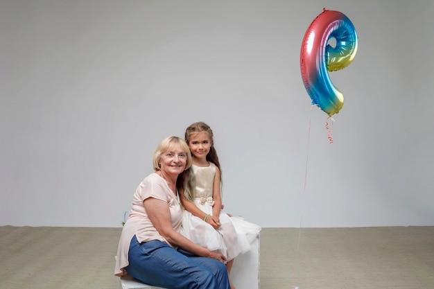 Garota com cabelo comprido em um vestido festivo com a vovó sênior com fundo branco foto em estúdio familiar