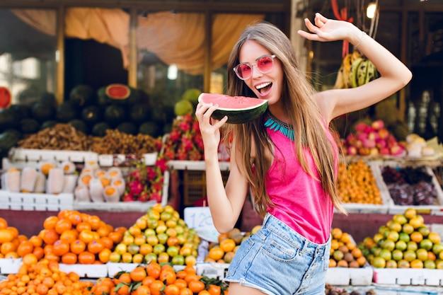 Garota com cabelo comprido no mercado com mercado de frutas tropicais. ela vai provar uma fatia de melancia na mão
