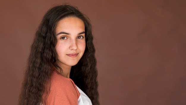 Garota com cabelo comprido, olhando para a câmera