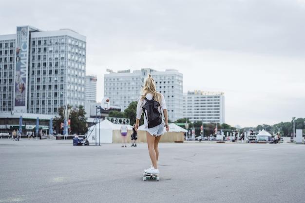 Garota com cabelo comprido patina em um skate. rua, esportes ativos