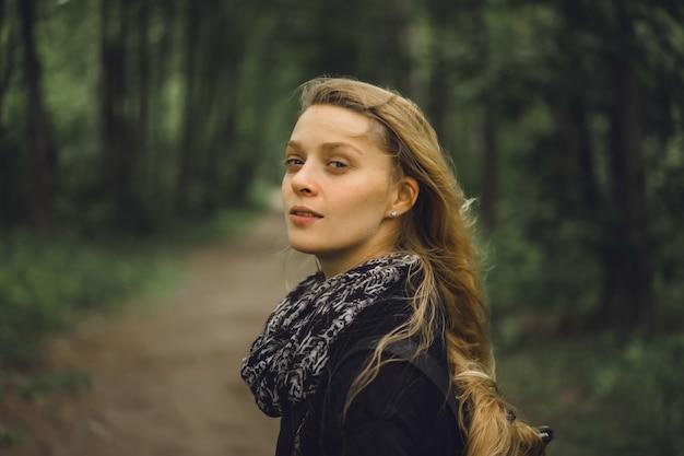 Garota com cabelo comprido percorre a floresta.
