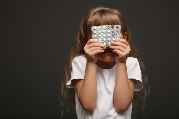 Garota com cabelo comprido segura comprimidos e esconde o rosto.
