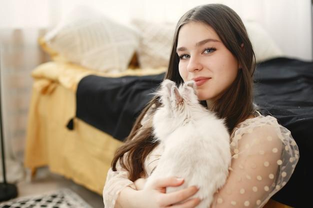 Garota com cabelo comprido, segurando um coelho branco.