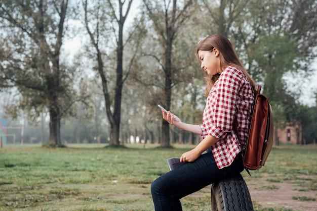 Garota com cabelo comprido, verificando seu telefone