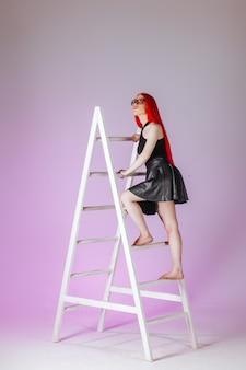 Garota com cabelo comprido vermelho usando óculos e saia de couro sobe uma escada em um fundo rosa