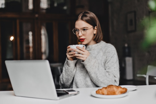 Garota com cabelo curto e reto, vestida com um suéter cinza bebe chá, olha para a tela do laptop. foto de mulher com batom vermelho de óculos, sentado à mesa com croissant no prato.