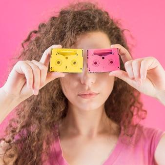 Garota com cabelo encaracolado, cobrindo o rosto com fitas
