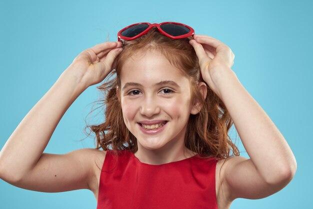 Garota com cabelo encaracolado, óculos de sol, vestido vermelho e diversão infantil azul