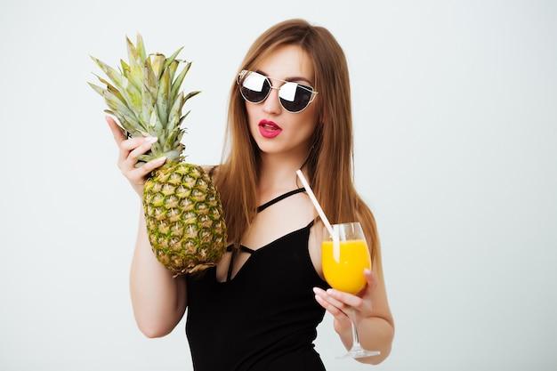 Garota com cabelo escuro, vestindo um maiô sexy modelo posando com um abacaxi