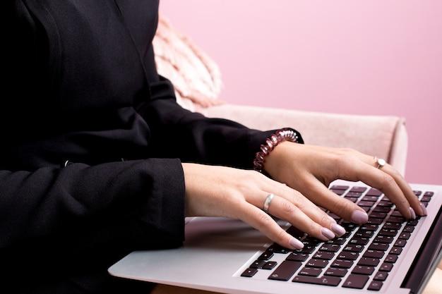 Garota com cabelo loiro trabalha em um laptop em um quarto-de-rosa