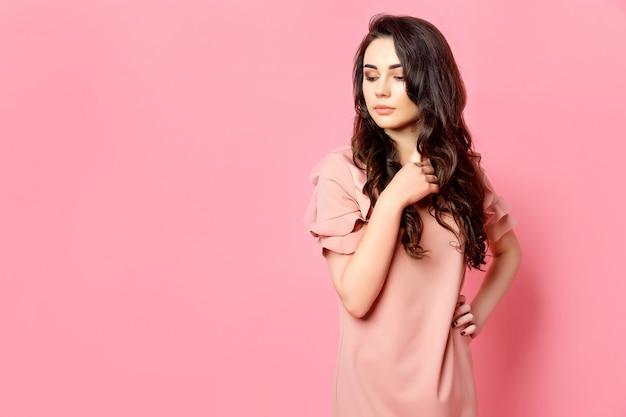 Garota com cabelo longo cacheado em um vestido rosa.