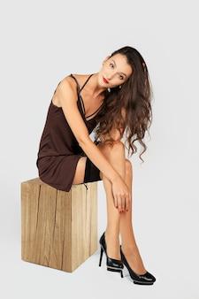Garota com cabelo longo cacheado, sentado no vestido curto e meias com liga