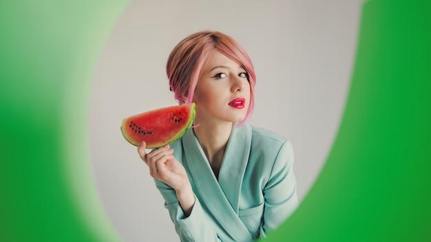 Garota com cabelo rosa e casaco azul segurando melancia
