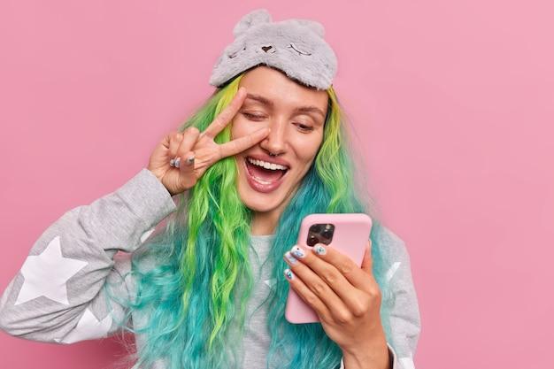Garota com cabelo tingido faz gesto de paz no olho segura celular leva selfie usa roupa de dormir máscara de dormir na testa posa rosa