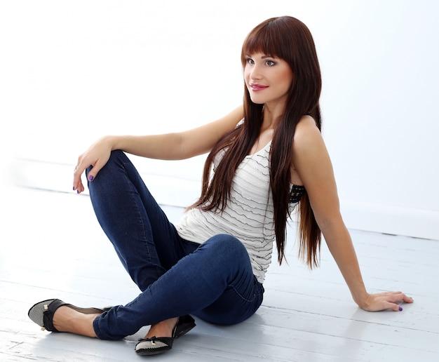 Garota com cabelos longos, sentada no chão