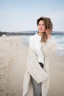 Garota com cabelos ondulados ao lado do mar