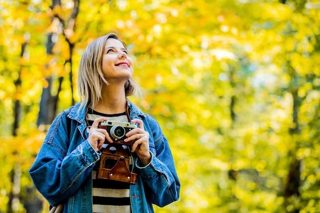 Garota com câmera vintage tem descanso no parque no outono temporada tempo