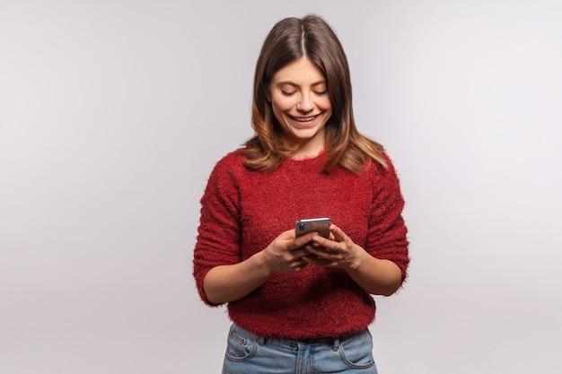 Garota com celular sorrindo digitando ou lendo mensagem engraçada na rede social