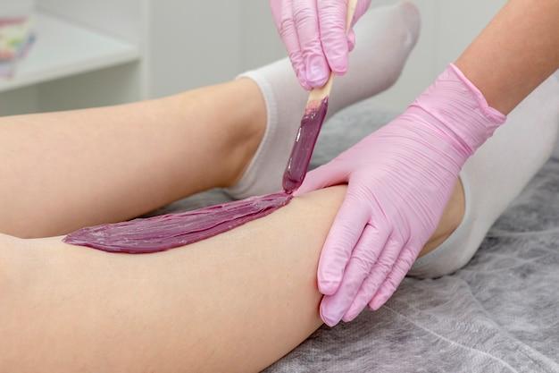 Garota com cera de pernas fazendo depilação em centro de spa