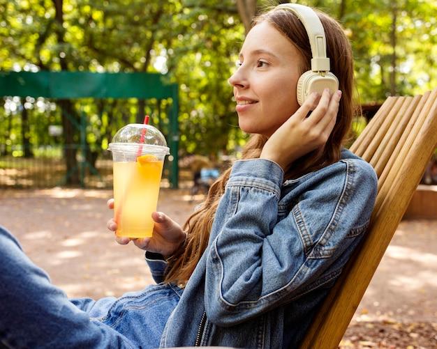 Garota com fones de ouvido bebendo suco fresco