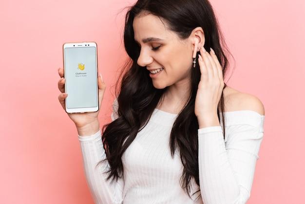 Garota com fones de ouvido está segurando um smartphone com o aplicativo clubhouse na tela.