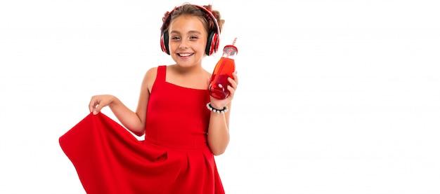 Garota com longos cabelos loiros, pontas tingidas de rosa, recheada em dois tufos, vestido vermelho, com fones de ouvido vermelhos, pulseira, em pé e segurando o telefone na mão e bebe suco na garrafa de vidro com um tubo